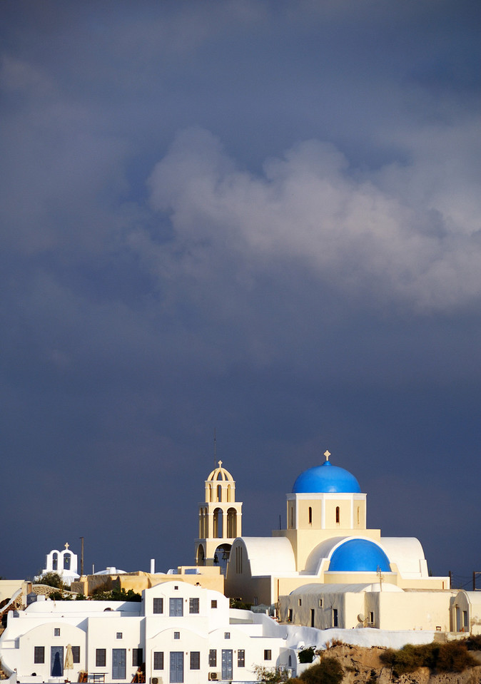 Storm clouds loom in mid-morning light above a church in Oia, Santorini