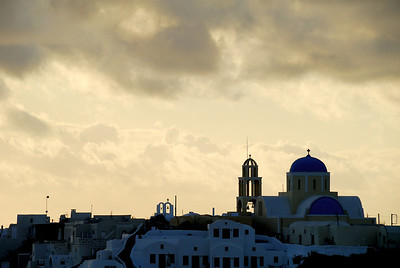 Late afternoon clouds over a church in the village of Oia