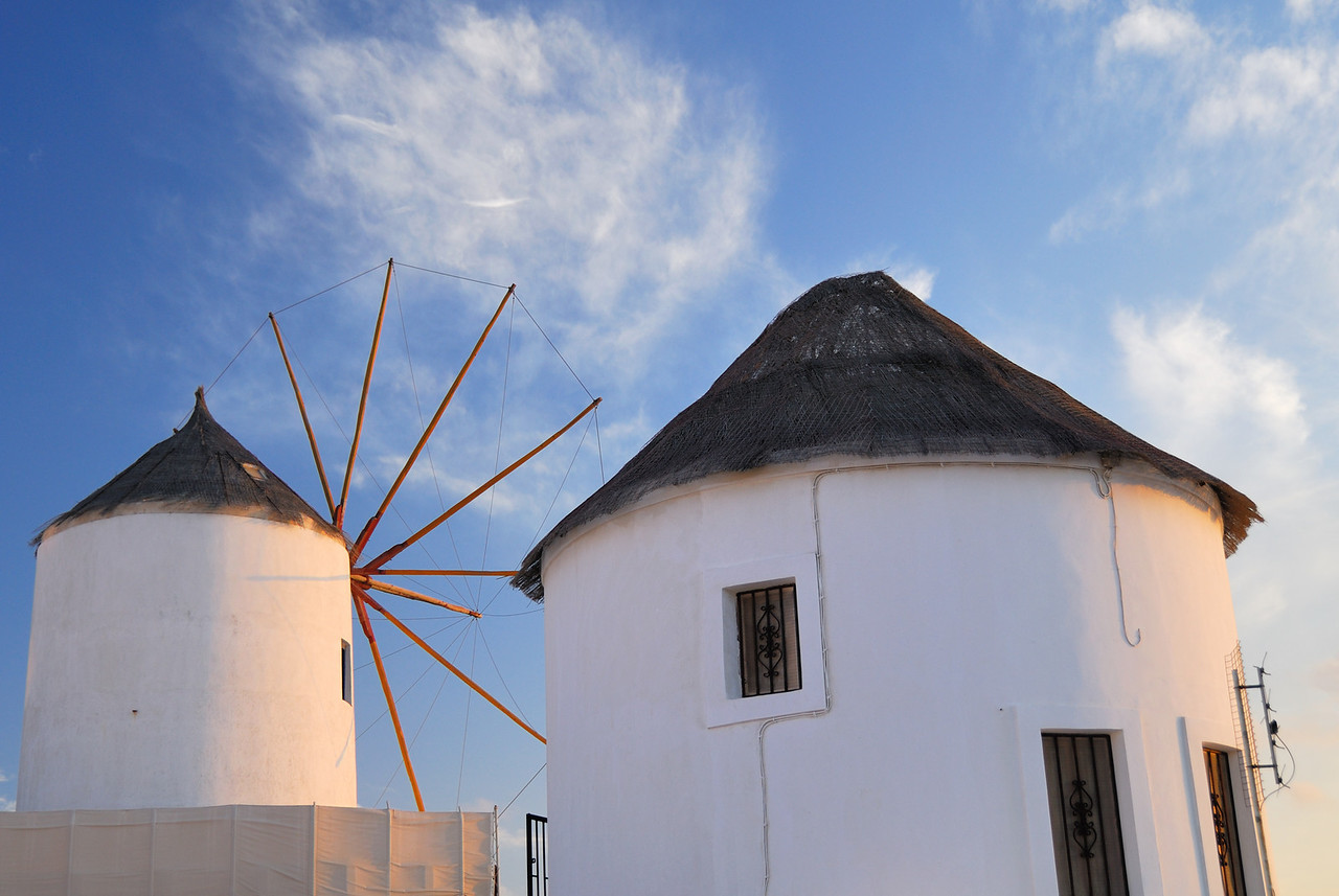 Windmill and converted house at sunset in the village of Oia
