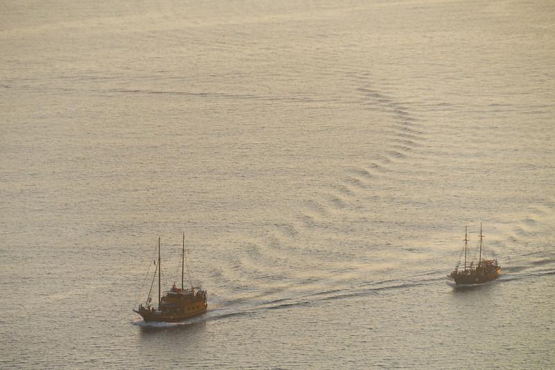 Two boats cruising the Santorini caldera at sunset