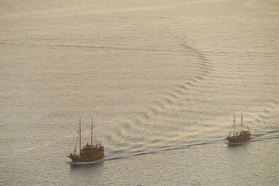 Two boats cruising the Santorini caldera at sunset