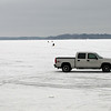"This truck is parked quite a ways ""offshore"" on the frozen lake.  You can see some individual ice fishermen farther out."
