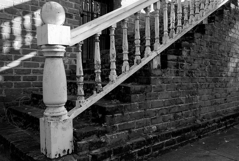 B&W railing stairs wooden bannister peeling white paint bricks shadow travel USA savannah georgia