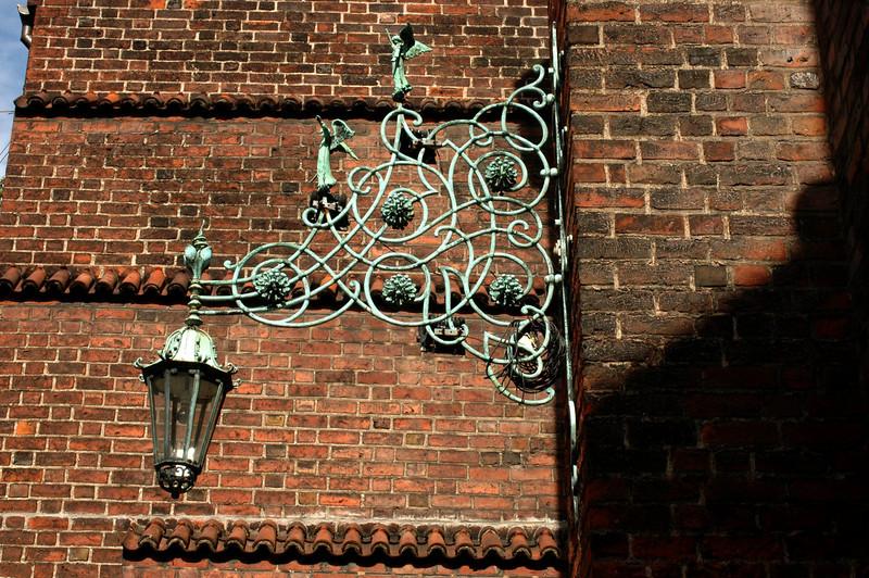 Ironwork light fixture on church facade.