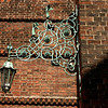 Ironwork light fixture on church facade.