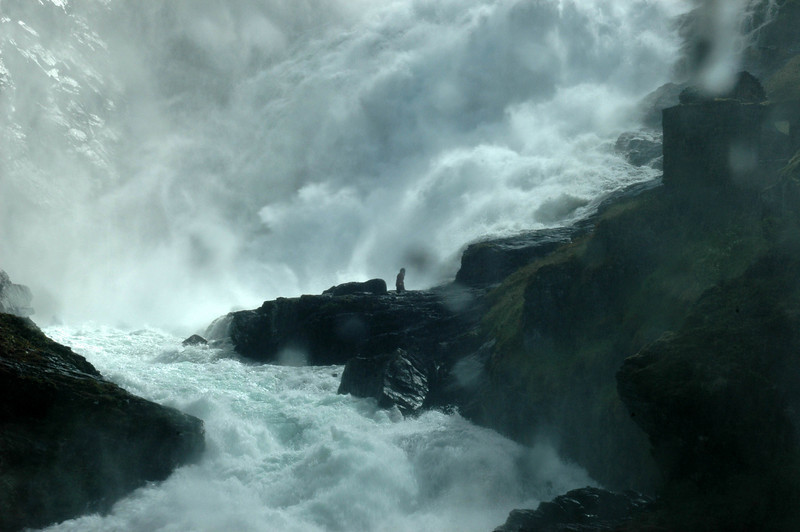 Into the Norwegian fjords. We took a narrow gauge friction railway down to the village of Flam. This was the base of a waterfall along the route. Note woman on the spit of land - she was singing something, mostly drowned out by the roar of the falls.