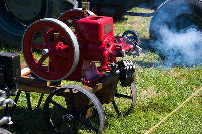 I have no idea what this engine is supposed to DO, but it would clunk along, and about every 20 seconds, it would make a popping sound and spew a little cloud of smoke. I had to watch the little workings for a bit to get the pattern so I could time the shot right.  Taken at Antique Engine and Tractor Show - Somers, CT, US