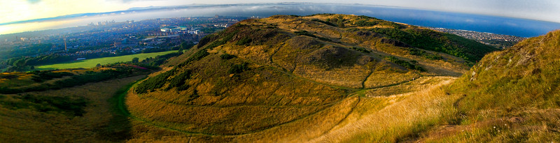 A view of the trails climbing up Arthur's Seat, with the ocean and Edinburgh city in the background