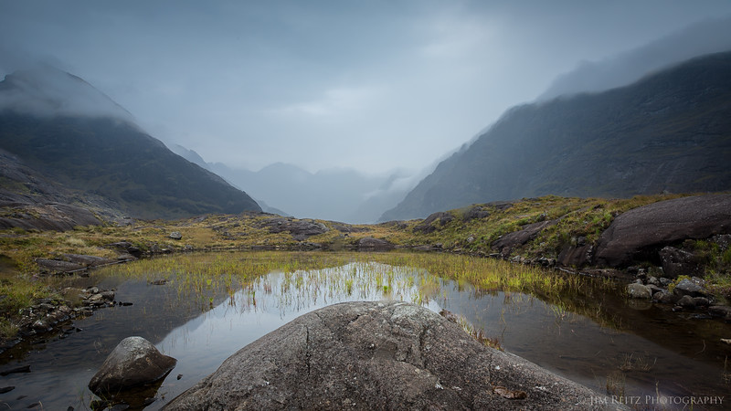 The Cuillin mountains and reeds are reflected in pond at Loch Coruisk, Isle of Skye, Scotland