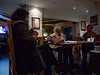 Chums chatting and playing music in a pub in Pithlochry