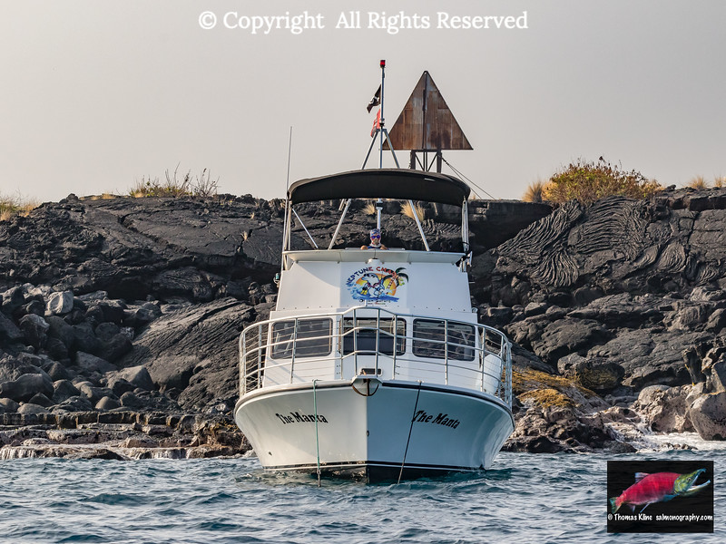 Charter boat by lava flow formation