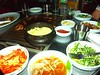 A typical Korean meal for 2.<br /> <br /> Kimchi on the lower-left, teriyaki onions at the bottom, a salad on the lower right, meat on the grill and eggs coking in a pot, and other assorted dishes populate the table.