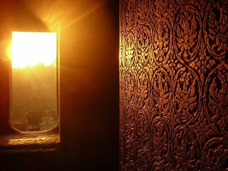 The sun rises through the mist.<br /> Light reflects off a wall.<br /> And Angkor emerges from the darkness.