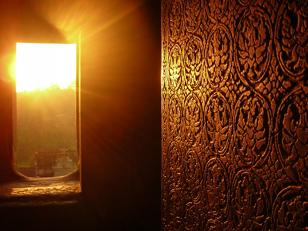 The sun rises through the mist. Light reflects off a wall. And Angkor emerges from the darkness.