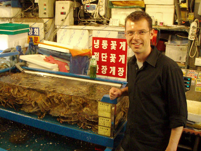Frederick at the Seoul Fish Market, posing next to some crabs