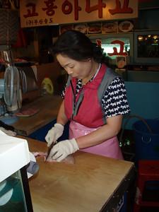 Vendor at the Seoul Fish Market preparing sashimi from a live fish we just bought