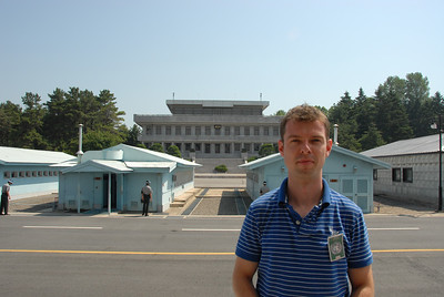 Frederick at the Military Demarcation Line in the Korean Demilitarized Zone. The blue UN buildings are on top of the border while the large building behind it is in North Korea.