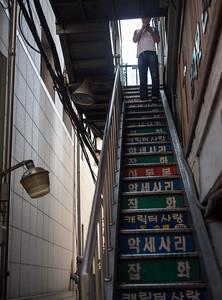 Man texting on coloured stairs.  Namdaemun market.