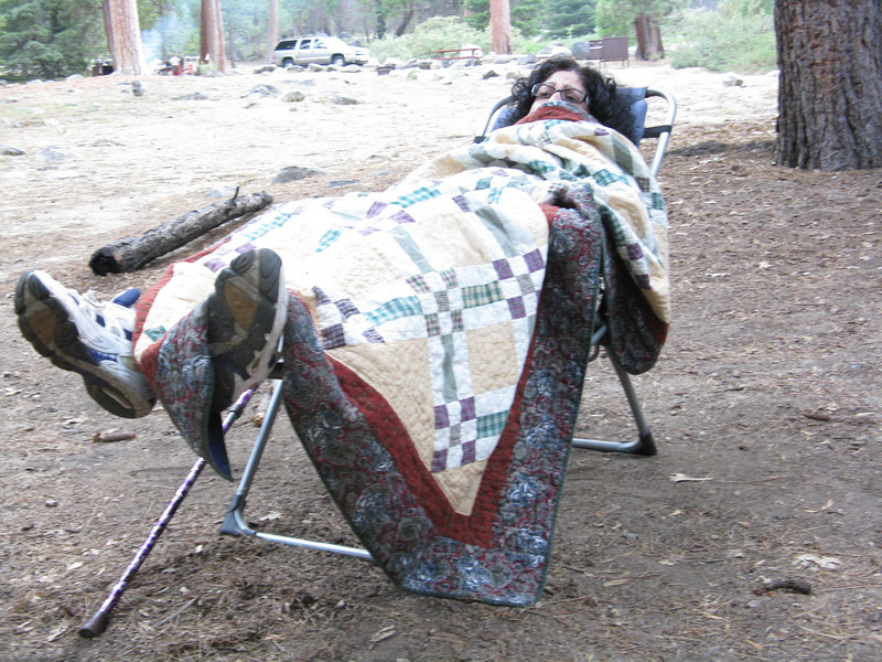 Christine elevating her knees in the campground. It wasn't cold, but the quilt kept the bugs away.