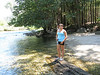 Marissa on a big rotted out log in the river next to a nice sandy shore.