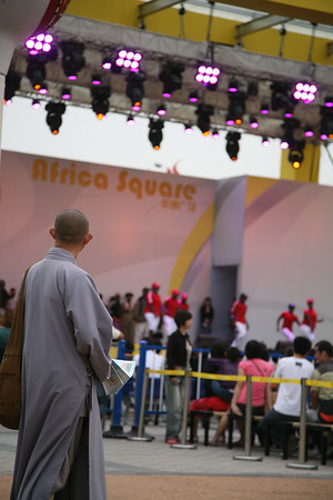 A Young Monk Watching African Dance at Shanghai World Expo