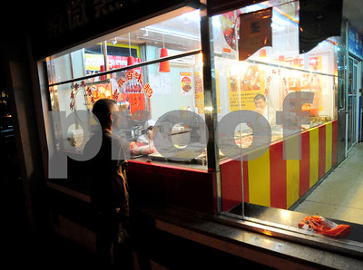 August 2010-Shanghai, China- The people in Shanghai, China, find a way to carry on with temperatures in excess of 108 degrees and heavy humidity.   A man looks inside a fast food restaurant as both employees talk on their cell phones.  Photo by SMP   ZUMA Press