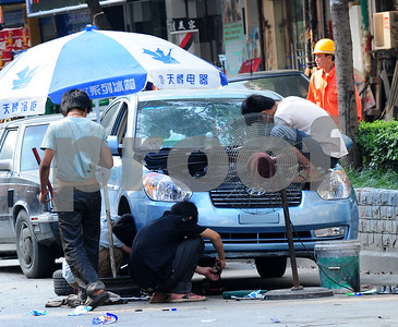 August 2010-Shanghai, China- The people in Shanghai, China, find a way to carry on with temperatures in excess of 108 degrees and heavy humidity.   Four young men working on a car just before dusk, with a large outdoor fan running on high to provide some relief from the high temperatures.  Photo by SMP   ZUMA Press