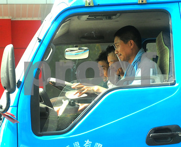 August 2010-Shanghai, China- The people in Shanghai, China, find a way to carry on with temperatures in excess of 108 degrees and heavy humidity.   Three men, sitting in traffic, under a scortching hot sun, at the end of a long work day.  Photo by SMP   ZUMA Press