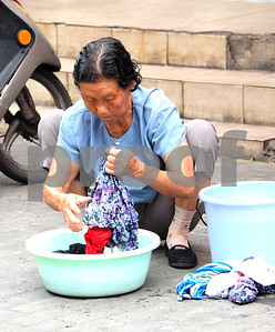 August 2010-Shanghai, China- The people in Shanghai, China, find a way to carry on with temperatures in excess of 108 degrees and heavy humidity. An elderly woman washes her clothes on the street at the end of the day and temperatures are still above 90 degrees.   Photo by SMP   ZUMA Press