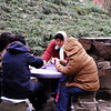 Four women playing card. They wearing like bear to play outside, where was so cold. Have good time.