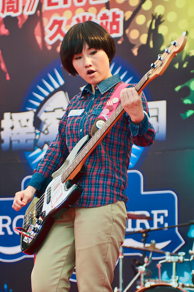 The bass player of an all-female band playing at one of the Shanghai's shopping centres.
