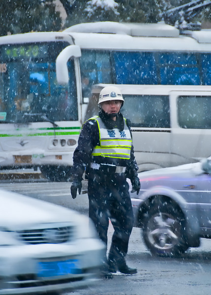 Police keep the traffic flowing in a snowy Shanghai.