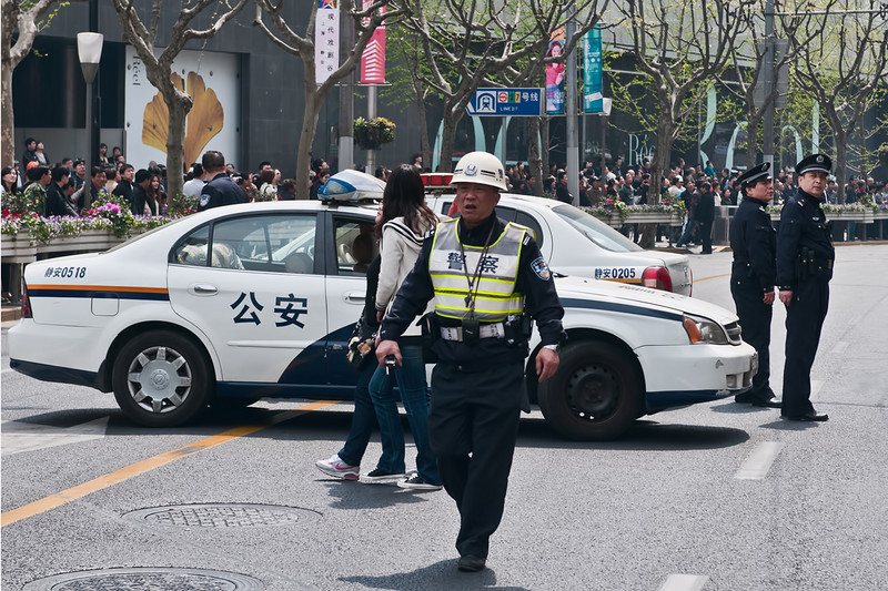 A police supervisor barks orders as one of Shanghai's busiest streets is blocked due to a fire.