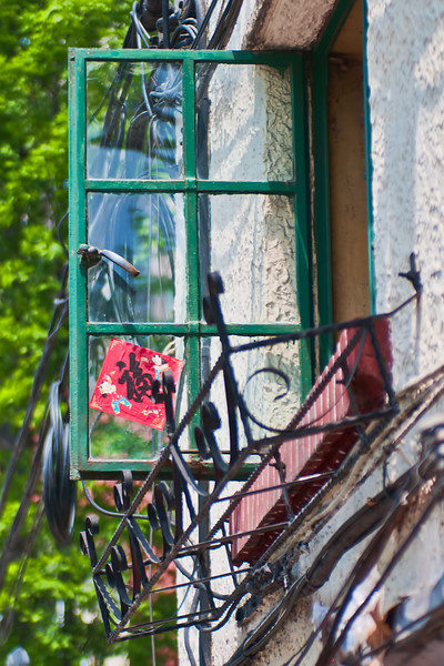 A typical window in the French Concession let's in some fresh air on a warm spring day.  The red sticker is a good luck charm.