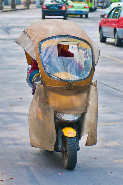 Shanghai's streets are filled with a wide variety of vehicles.  This is a modified scooter, presumably designed to guard against inclement weather.