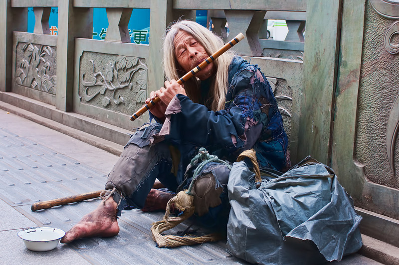 This street musician was found in central Shanghai, near a famous temple.  Note the wardrobe!