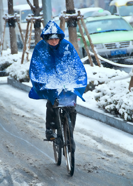 He looks miserable trying to navigate through the snow of Shanghai on his bicycle.