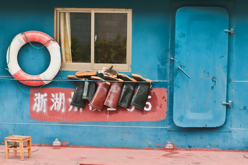 Several pairs of boots air on the deck of a working barge on Shanghai's Hongqiao River.
