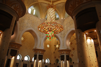 The viewer is amazed by the sheer beauty of the mosque and then looking up they see this!  Its a chandelier that looks like someone's painted tennis balls and hung them off the ends. At the top of the picture you can see the huge gallery that encircles the prayer hall.