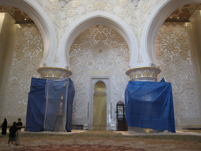 The wall showing the 99 Names or attributes of God.  The gold niche in the centre is called the 'mihrab' and it shows worshippers the direction of Mecca.  The brown chair with stairs next to the mihrab is the 'minbar' which serves the same purpose as a pulpit in a church and is where the imam speaks to the people.