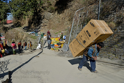 People of the hills carry lots of weight. This man is carrying a Samsung refrigerator on his back. Shimla is the capital city of the Indian state of Himachal Pradesh, located in northern India at an elevation of 7,200 ft. Due to its weather and view it attracts many tourists. It is also the former capital of the British Raj.