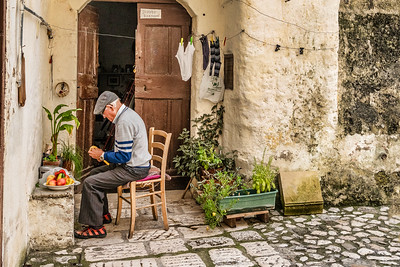 An artisan working on his craft in front of his house.