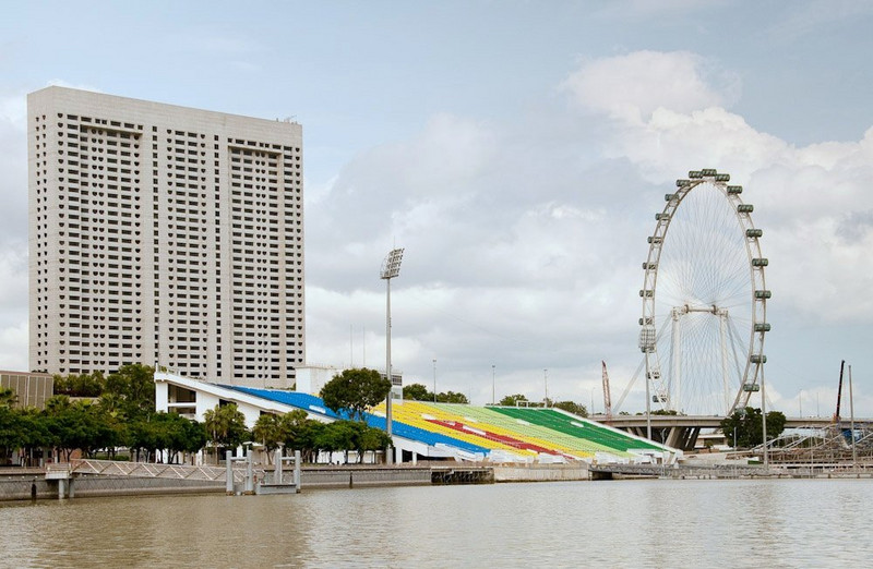 The Singapore Flyer, world's largest Ferris Wheel, as seen from a water taxi on Marina Bay, at the mouth of the Singapore River. The  brightly colored structure is the grandstand of the Marina Bay Floating Stadium. It faces on the largest floating performance stage in the world. At the time of this photo, the stage was configured as a soccer pitch.