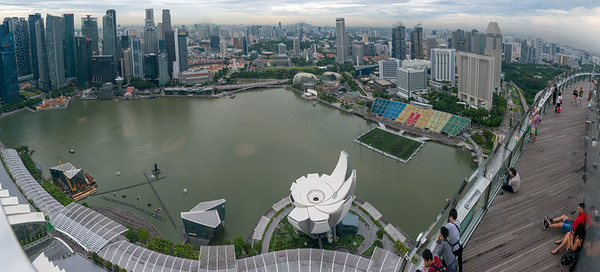 Panoramic aerial view of Marina Bay in the evening, from Sands SkyPark Observation Deck, on the 57th floor offering panoramic city views & 2 upscale restaurants and a pool for hotel residents. Singapore.