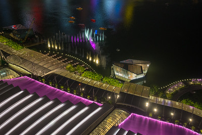 """Spectra - A Light And Water Show"" and CBD Singapore, seen from in ariel view from Sands SkyPark Observation Deck on the 57th floor. The deck has panoramic city views & 2 upscale restaurants and a pool for hotel residents."