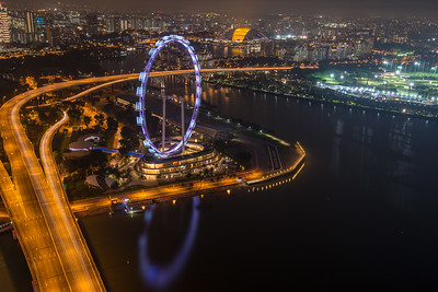 Ariel view of Singapore Flyer in central Singapore, adjacent to the Marina Reservoir. The Singapore Flyer is a giant Ferris wheel in Singapore.  Seen from Sands SkyPark Observation Deck on the 57th floor. The deck has panoramic city views & 2 upscale restaurants and a pool for hotel residents.