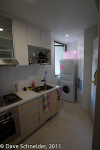 "The kitchen looking in from the ""dining room"". Unfortunately, the floor was terminally damaged by the owners when doing their initial cleanup when the apt was new. Sigh. It's 3 years old now. Love the trash chute by the washer."