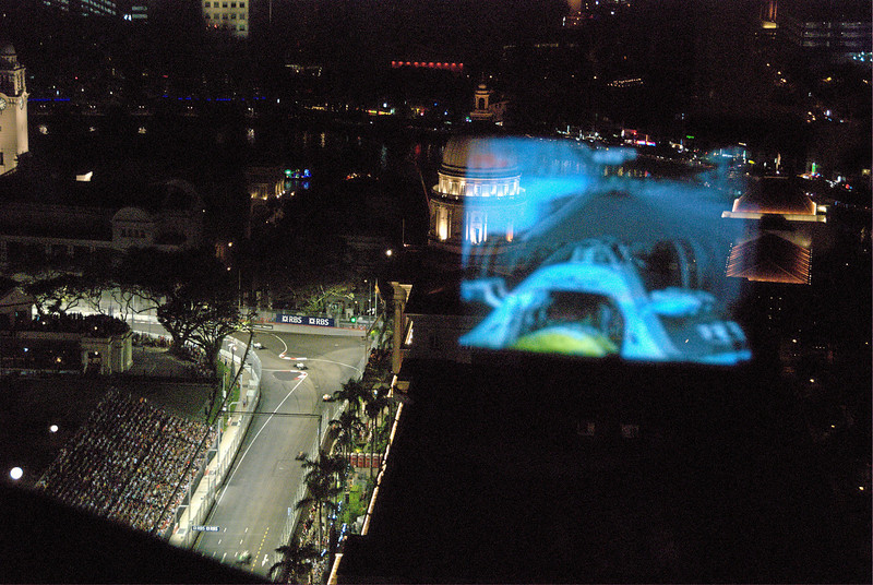 Looking at the track, with reflection of television showing the race