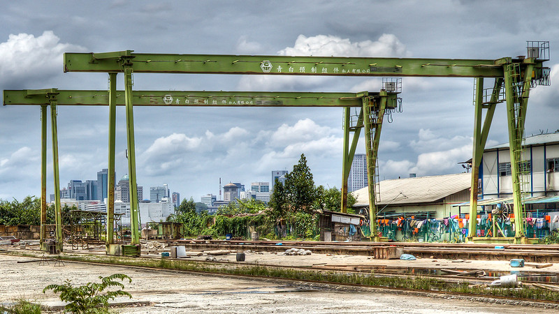 Redundant yard in Singapore with Johor (Malaysia) in the background and workers accomodation on the right