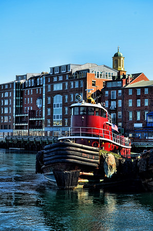 Portsmouth, New Hampshire skyline with tugboat in foreground.